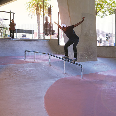 Buy stock photo Shot of a skateboarder performing a trick on a rail
