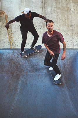 Buy stock photo Shot of two young men skating at the skatepark