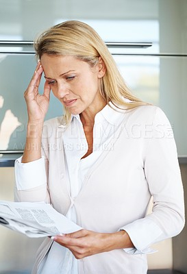 Buy stock photo Portrait of a thoughtful businesswoman touching her head while reading a document