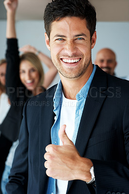 Buy stock photo Portrait of smiling business man showing a thumbs up with excited colleagues at the back
