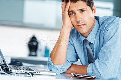 Buy stock photo Businessman sitting at desk with hand on his face, looking worried