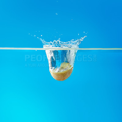 Buy stock photo Half kiwi immersed in water against background