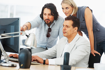 Buy stock photo Young man pointing at computer explaining business plan to his team