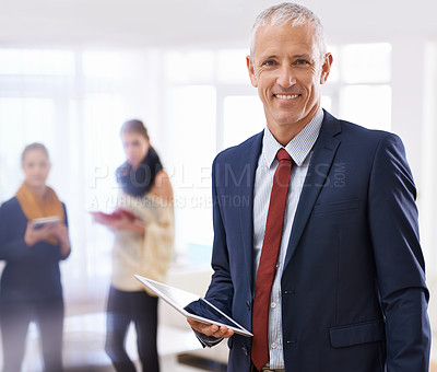 Buy stock photo Shot of a mature businessman standing in the foreground with two colleagues behind him