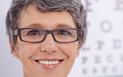 Buy stock photo Closeup of a mature female wearing glasses standing in front of an eye test poster