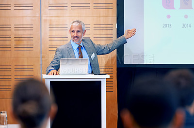 Buy stock photo A mature businessman gesturing while giving a presentation at a press conference
