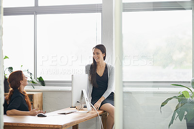 Buy stock photo Shot of two businesswomen having a friendly conversation at the desk
