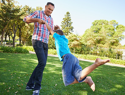 Buy stock photo A father swinging his young son around as they play in the park on a beautiful sunny day