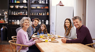 Buy stock photo Portrait of a family eating breakfast around the kitchen table
