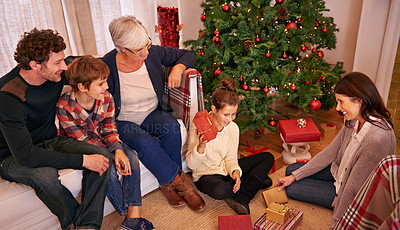 Buy stock photo High angle shot of a family opening gifts on Christmas morning