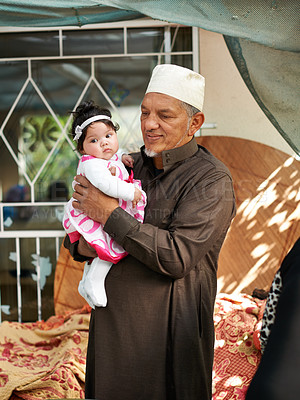 Buy stock photo Shot of a grandfather holding his granddaughter