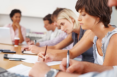Buy stock photo Focus on business woman with colleagues writing notes in meeting