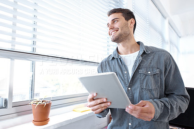 Buy stock photo Low angle shot of a young designer holding a digital tablet and looking out a window