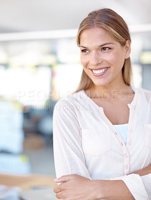 Buy stock photo Shot of a young female business professional standing in an office with her arms crossed