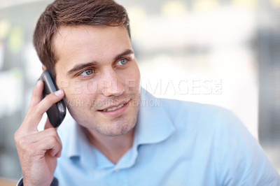 Buy stock photo Handsome young businessman looking sideways while chatting on his cellphone