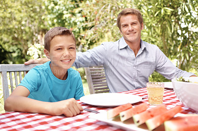 Buy stock photo A father and son sitting at the lunch table together