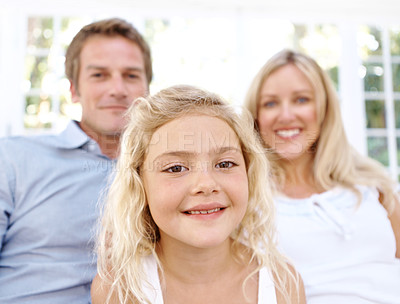 Buy stock photo Portrait of a smiling blonde girl with her parents sitting behind her