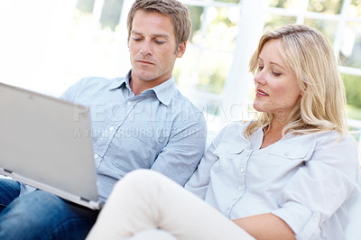 Buy stock photo A couple looking at a laptop while sitting on the couch