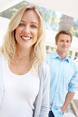 Buy stock photo Portrait of a smiling woman with her husband standing in the background