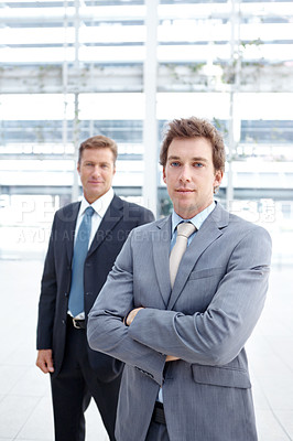 Buy stock photo A dedicated young executive crossing his arms while a colleague stands in the background