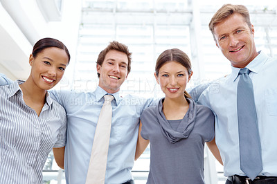 Buy stock photo A successful business team hugging one another and celebrating