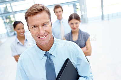 Buy stock photo A handsome businessman smiling at the camera with his team in the background