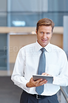 Buy stock photo A handsome businessman working on his digital tablet while looking at the camera