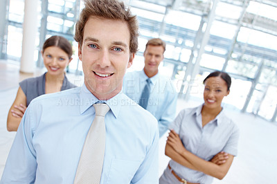 Buy stock photo Handsome young businessman smiling with his team behind him