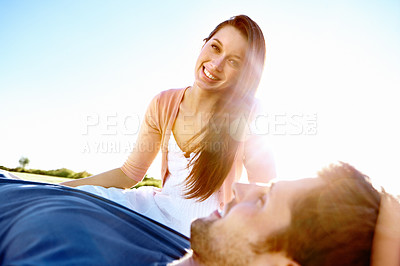 Buy stock photo Low angle portrait of a young man lying on the grass with his girlfriend sitting up behind him