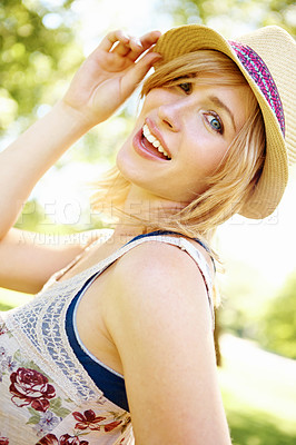 Buy stock photo Portrait of a fun-loving woman posing and holding on to her hat in the outdoors