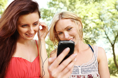 Buy stock photo Two beautiful friends listening to music in a park