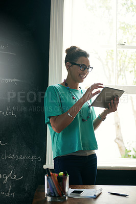 Buy stock photo Cropped shot of an attractive young woman holding a digital tablet