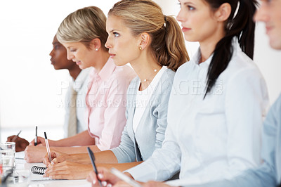 Buy stock photo Successful group of business people writing notes at seminar