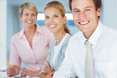 Buy stock photo Successful young male business executive sitting with his colleagues