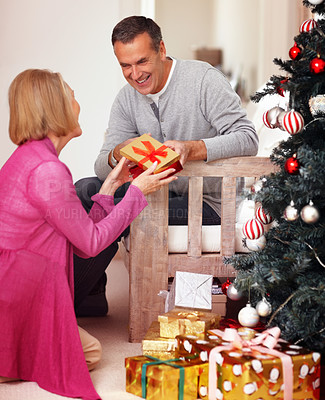 Mature woman giving Christmas present to husband at home