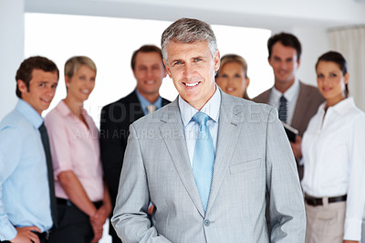 Buy stock photo Portrait of a senior manager smiling and his team standing behind him at office