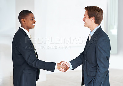 Buy stock photo Two business colleagues standing together and shaking hands at office