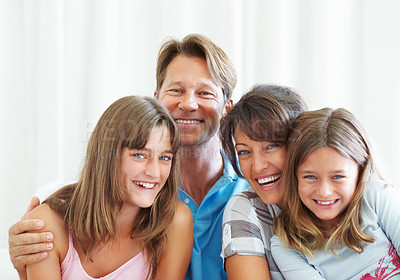 Buy stock photo Portrait of family sitting together on a sofa and smiling