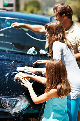 Buy stock photo Two young girls helping their father to wash their family car