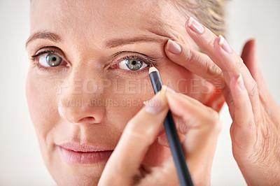 Buy stock photo Cropped studio shot of a mature woman applying eyeliner