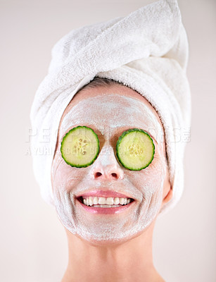 Buy stock photo Cropped shot of a mature woman with a mask applied to her face and cucumber slices on her eyes