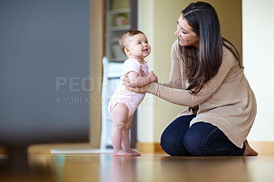 Buy stock photo Shot of a mother helping her baby girl stand