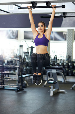 Buy stock photo Full length shot of a young woman doing pull ups in the gym