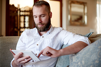 Buy stock photo Shot of a young man using a digital tablet at home on the sofa