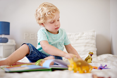 Buy stock photo Shot of a little boy playing with his toys at home