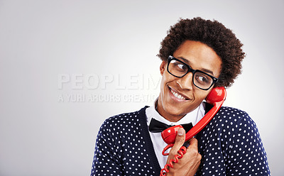 Buy stock photo Studio shot of a young man talking on an old telephone