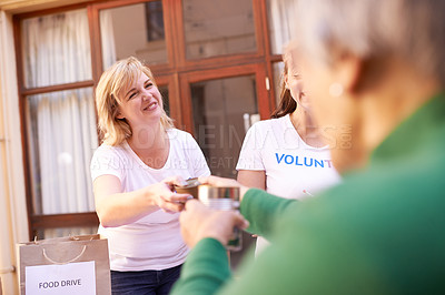 Buy stock photo Cropped shot of volunteers doing charity work at a nursing home