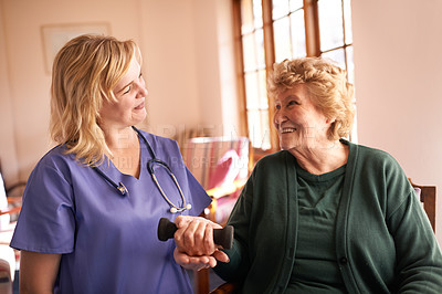 Buy stock photo Shot of a healthcare worker encouraging a senior woman to exercise at a retirement home