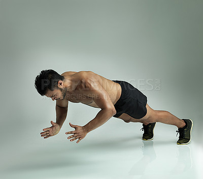 Buy stock photo Studio shot of a young man doing a clap pushup against a gray background