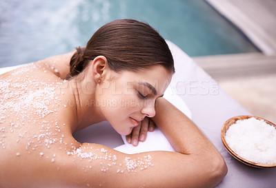 Buy stock photo Shot of a young woman enjoying a salt exfoliation treatment